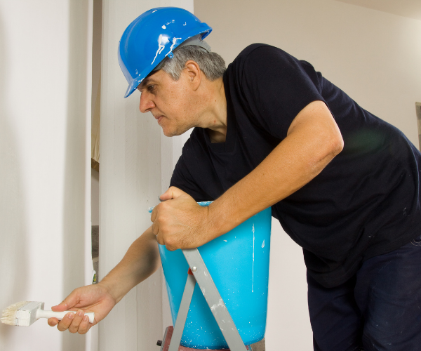 Interior house painter painting a wall inside a house